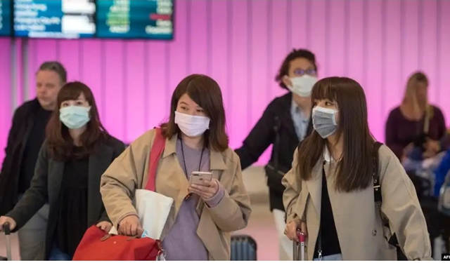 乘客们在抵达加州洛杉矶国际机场时戴上防护口罩,以防冠状病毒的传播